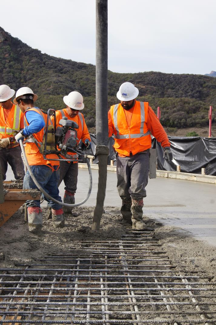 Crew filling rebar with the concrete through concrete snorkel