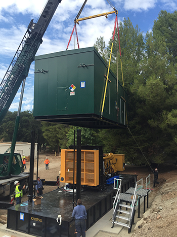 The generator's protective housing being lowered into place